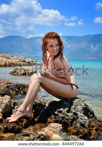 Young beautiful sexy girl in bikini sitting at rocks near blue green clear sea water. Sunbathing woman - stock photo