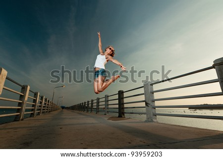 Young beautiful sexy smiling woman jumping in sunset light on a pier, holding watermelon heart - stock photo