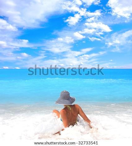 Young beautiful sexy tanned blond woman in bikini in the sea - stock photo