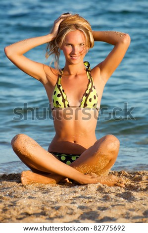 Young beautiful sexy tanned blond woman in bikini sitting on sea beach - stock photo