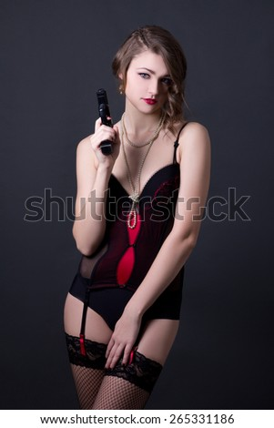 young beautiful sexy woman in lingerie posing with gun over grey background - stock photo