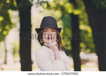 Young beautiful sexy woman in stylish straw fedora hat showing hush sign with finger at her red lips, making silence gesture - secret, mystery, adultery concept - stock photo