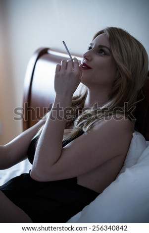 Young beautiful sexy woman smoking cigarette in bed - stock photo