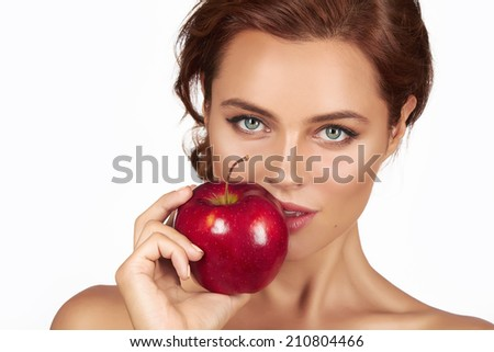Young beautiful sexy woman with dark curly hair, bare shoulders and neck, holding big red apple to enjoy the taste and are dieting, healthy eating and organic foods, feeling temptation, smile, teeth