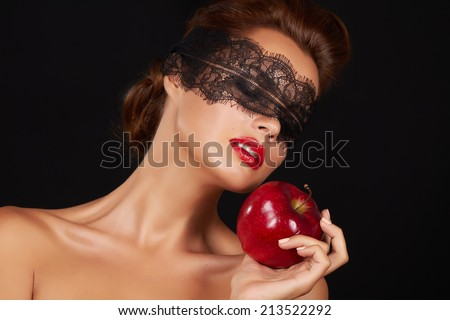 Young beautiful sexy woman with dark lace on eyes bare shoulders and neck, holding big red apple to enjoy the taste and are dieting, feeling temptation, teeth passion sex red lips  - stock photo