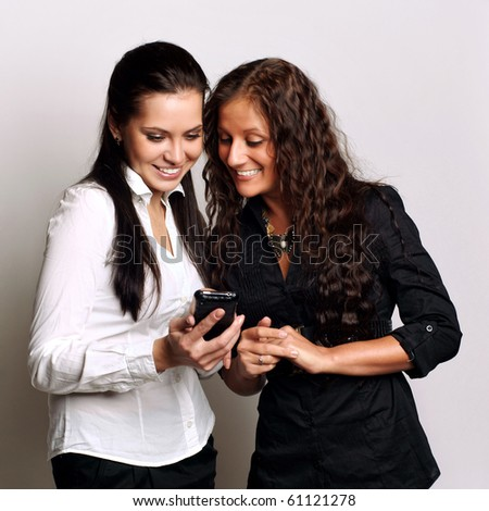 young beautiful sisters using the cellphone to send and receive sms