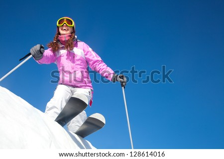 young beautiful skier rides a ski resort on a background of blue sky - stock photo