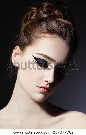 Young beautiful slim woman with fancy cat eye make-up and stylish hairdo - stock photo