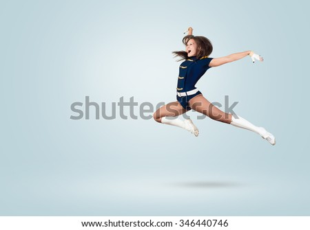 Young beautiful smiling cheerleader girl jumping high - stock photo