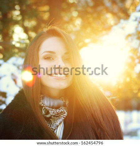 young beautiful smiling girl portrait in winter forest
