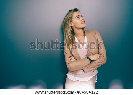 young beautiful smiling girl with blonde hair looking up while posing on a gray background with copy space area for your text o design. - stock photo