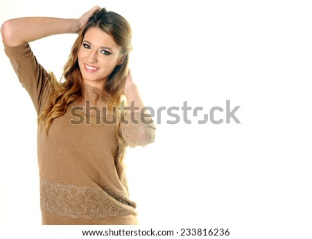 Young beautiful smiling long haired blond girl posing with her hands behind her head wearing a beige dress isolated on White background - stock photo