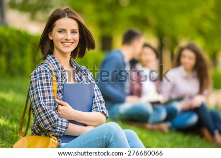 Young beautiful smiling student sitting on the lawn with friends and reading. - stock photo