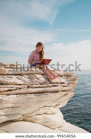 Young beautiful smiling teenage girl with computer on the beach/rocks with sea-view - stock photo