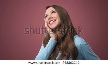 Young beautiful smiling woman daydreaming with hand on cheek - stock photo