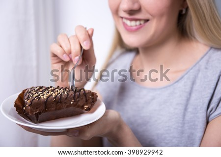 young beautiful smiling woman eating chocolate cake at home - stock photo