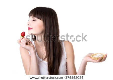 Young beautiful smiling woman eating strawberry decoration from delicious cream tart cake which she is holding in her hand, studio, white background, isolated - stock photo