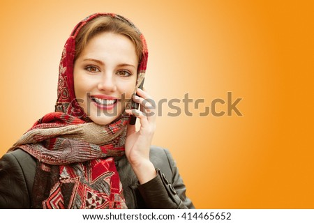 Young beautiful smiling woman in motley red headscarf talks on cellular telephone isolated on orange background.