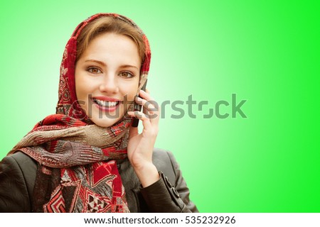 Young beautiful smiling woman in motley red headscarf talks on cellular telephone on a green background.