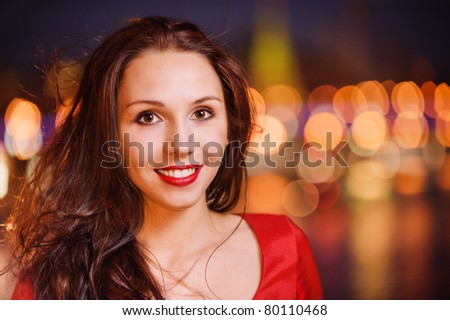 Young beautiful smiling woman in red dress against night of Moscow Kremlin. - stock photo