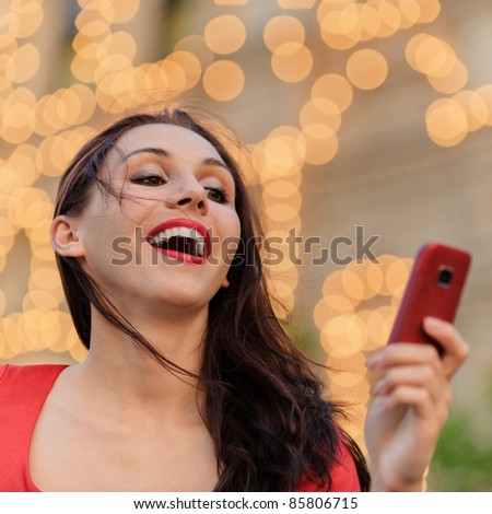 Young beautiful smiling woman in red dress reads text message on mobile phone against evening illumination. - stock photo