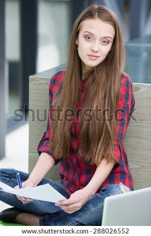 Young beautiful smiling woman sitting with sheet of paper and writing. - stock photo