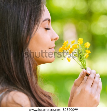 Young beautiful smiling woman smells small bouquet of yellow florets, against green summer garden.
