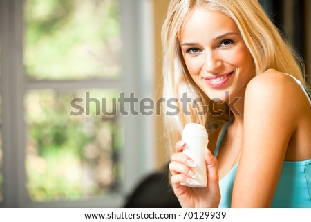 Young beautiful smiling woman with moisturizer, at home - stock photo