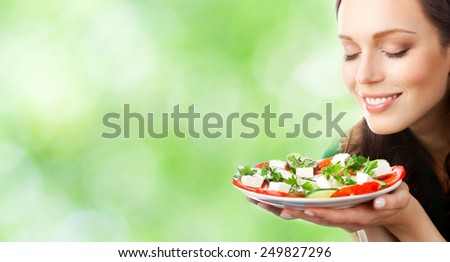 Young beautiful smiling woman with plate of salad, outdoor, with copyspace area for slogan or text - stock photo