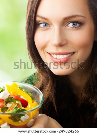 Young beautiful smiling woman with salad, outdoor - stock photo