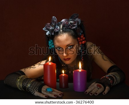 young beautiful soothsayer with three candles on dark red background - stock photo