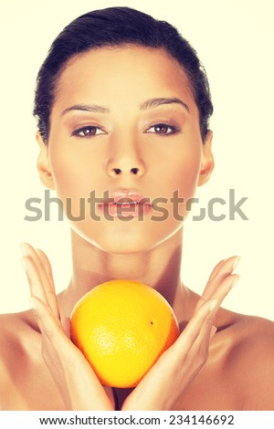 Young beautiful spa woman with orange in her hand, isolated on white - stock photo