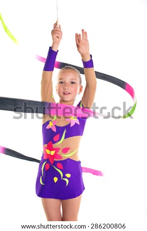 Young beautiful sport girl doing exercises with rainbow ribbon on rhythmic gymnastics event in elegant purple leotard suit dress isolated - stock photo