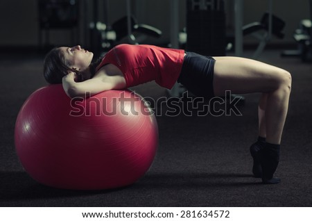 Young, beautiful, sports girl does exercises on a fitball at the gym. Toning. - stock photo