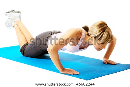 Young beautiful sportswoman exercising (doing push-up). - stock photo