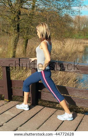 Young beautiful sportswoman lunging outdoors in a park. - stock photo