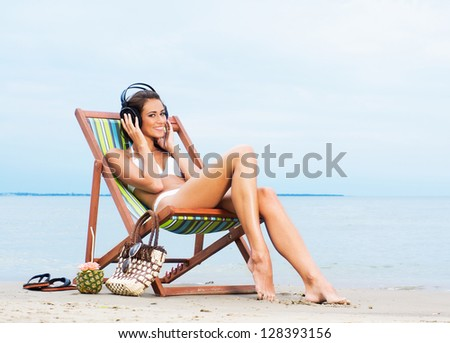 Young, beautiful, sporty and sexy woman listening to the music on the beach