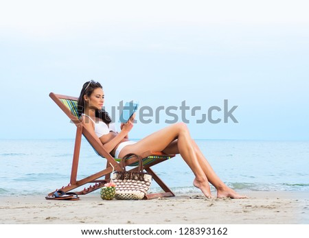 Young, beautiful, sporty and sexy woman reading on the beach - stock photo