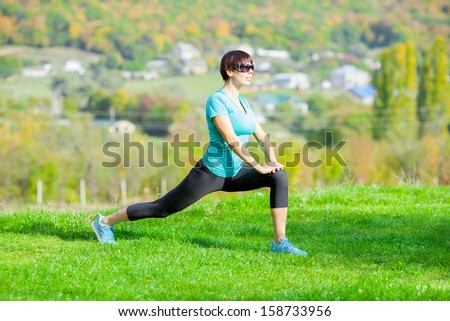 Young beautiful sporty woman doing fitness on green grass