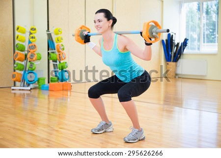 young beautiful sporty woman exercising with barbell in gym - stock photo