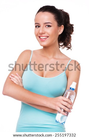 Young beautiful sporty woman holding a bottle of water, isolated on white background - stock photo