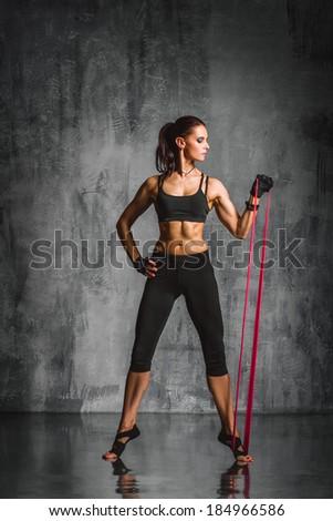 young beautiful sporty woman posing on studio background - stock photo
