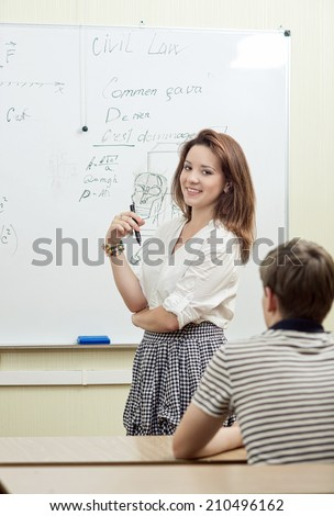 Young beautiful student answers in the classroom at the blackboard. Educational theme: girl  student in a classroom. - stock photo
