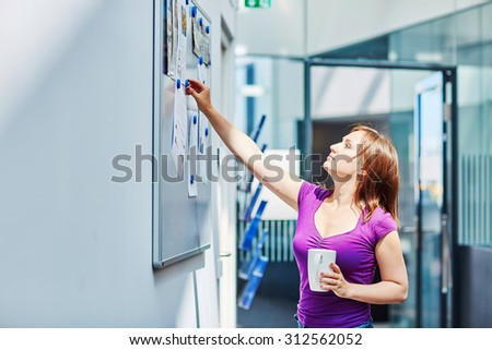 Young beautiful student at college or university using notice board - stock photo