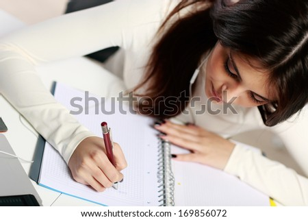 Young beautiful student doing her homework - stock photo