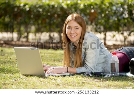 young beautiful student girl lying on park grass with computer laptop on rug studying happy preparing exam or surfing on internet in technology and education concept
