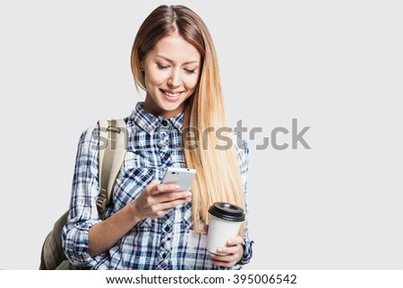Young beautiful student girl with smart phone and coffee - stock photo