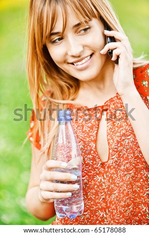 Young beautiful student in red clothes speaks on cellular telephone and has control over bottle with water, on green summer background. - stock photo