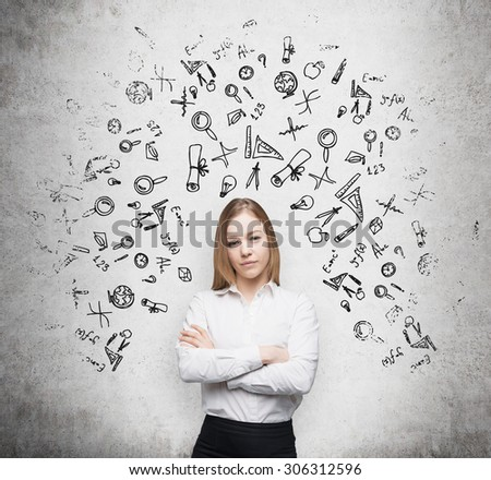 Young beautiful student is thinking about education at business school. Drawn business icons over the concrete wall. - stock photo
