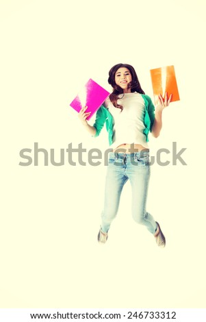 Young beautiful student jumping with files, workbook. - stock photo